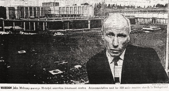 Warden John Moloney in front of Matsqui Institution, still under construction. Vancouver Sun, 8 October 1963.